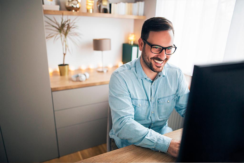Hombre sonriendo frente al ordenador